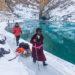 Personnes marchant sur de la glace au bord de l'eau.