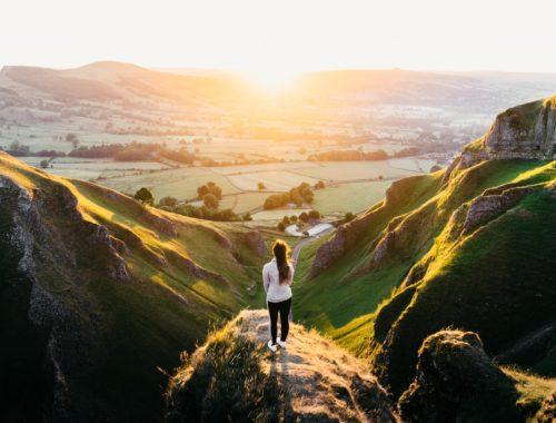 photo d'une femme sur un sommet regardant la nature